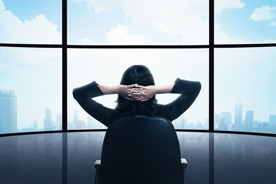 Business woman sitting on the chair looking the window. Business success conceptual